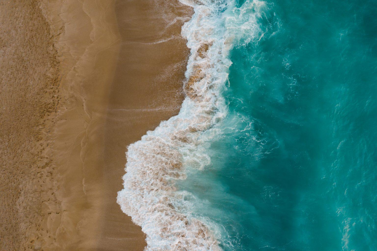 Blue sea wave on sandy beach. Sea shore top view